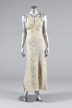 1936 - A gold and ivory lame court gown, bias-cut with ruched gathers