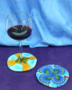 Circle wine coasters tutorial. Clever coasters with a pocket that you insert the base of your wine glass into, so that the coaster stays attached to the glass itself. These can be elegant or casual, depending on what fabrics you choose. The pattern will work with any small-medium scale print, as well as solids and batiks.