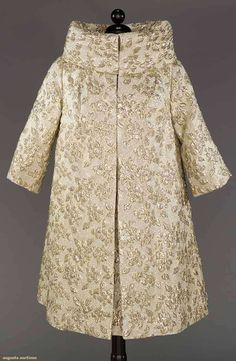 """WHITE & GOLD LAME EVENING OUTFIT, 1950s  -  Lot: 230 May 9, 2017 - CATALOG SALE Sturbridge, Massachusetts  -  """"Claralura California"""" white silk w/ small lattice lame ground, puffy lame flower blossoms & leaves, sleeveless dress, V neck, wide midriff band, matching A-line coat, large collar, 3/4 sleeves, B 38"""", W 29"""", Dress & Coat L 39"""", (few broken lame threads to dress) coat excellent; t/w 1 cap-sleeve dress of nearly identical fabric to dress & coat set above, excellent."""