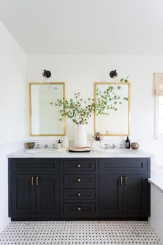 Rectangular brass mirrors lit by oil rubbed bronze and clear glass sconces fixed over a black oak dual washstand contrasted with a white marble countertop.