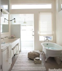 In the master bathroom of her light-filled home with a loft-like feel, photographer Amy Neunsinger combined an elegant claw-foot tub with a casual woven rug.   - HouseBeautiful.com
