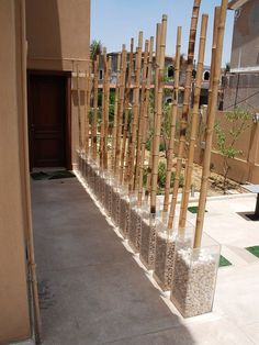 Outdoor DIY space divider using transparent vases and bamboo canes.