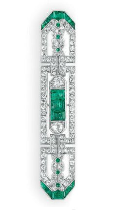 AN ART DECO DIAMOND AND EMERALD BROOCH   Designed as a single-cut diamond openwork plaque, bezel-set at the center with three rectangular-cut emeralds, flanked on either side by an old European-cut diamond, extending a line of single-cut diamond and collet-set emerald quattrefoils, the terminals decorated with calibré-cut emeralds, mounted in platinum, circa 1920