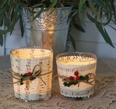 Candles in glasses wrapped with music sheets cut out with fancy scissors, tied with twine and berries.