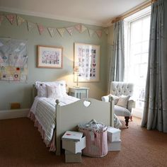 Susie Watson Designs - Susie Watson Designs Fabric Collection - A cream-grey wood bed with striped bedding, patterned bunting, a plain white armchair, white boxes and dark grey curtains