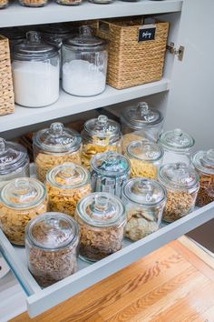 A pull out pantry shelf displays a collection of clear glass jars characterizing each snack with white lettering labels. Kitchen Organization Pantry, Home Organisation, Pantry Storage, Kitchen Pantry, Organization Hacks, Kitchen Decor, Freezer Organization, Organized Kitchen, Pull Out Pantry Shelves