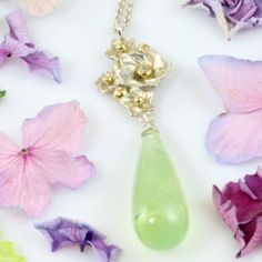 Small flowerbed with large green drop A bunch of silver flowers dripping a juicy, green prehenit-drop. Gold bubbles and a single diamond holds together the goodies ...