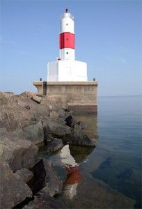PRESQUE ISLE HARBOR LIGHTHOUSE Located at the end of a rugged stone breakwater at Marquette's Presque Isle Park, the red beacon still guides ships day and night into the railroad ore docks. - Travel Marquette Michigan