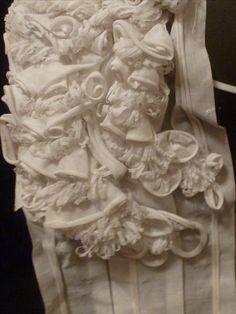 Oirschot poffer, overgang bloemen naar staarten. De stof om bloemen te maken wordt schuin geknipt en dan gerold. Je kunt er dan lussen of roosjes maken of rond een breinaald wikkelen. Allerlei versieringen zijn mogelijk. #NoordBrabant
