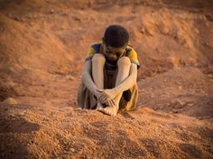 An exhausted boy sits on a mound of soil at Bilbalé. Image by Larry C. Price. Burkina Faso, 2013. #pulitzercenter #gold #childlabor