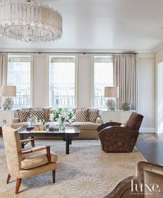 An NYC Apartment: In the living room: Extra-long sofas of Jeffrey's design were made by J&P Custom Upholstery and paired with Art Deco armchairs and parchment-clad cabinets designed by Jeffrey. The wool and silk carpet is from Doris Leslie Blau, and the chandelier is custom made of Brazilian rock crystal.
