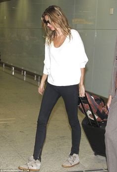 Returning to her roots: Gisele Bündchen hauled her own luggage trolley as she landed at Sã...