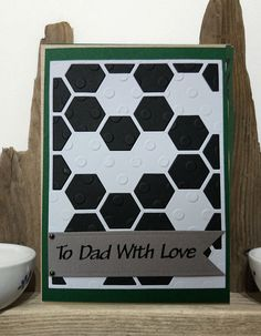 A lovely handmade Football theme card suitable for your Dads Birthday.  Black & White cardstock has been cut with the Stampin Up Big Shot Thinlits Hexagon Hive die and then embossed using the Craft Concepts Embossing Folder - More Dots - to add texture.  This has been mounted on grass-green cardstock and finished off with an To Dad With Love sentiment banner which has 2 black AB gems on.  The card measures approximately 10.5 x 14.8cm / 4 x 6, comes with an envelope and is blank insid...