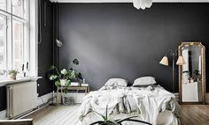 Consider this Scandinavian master bedroom an ideal case study for perfecting modern elegance. We're swooning over the coupling of the casual bedding situation and the ornate mirror set directly aside.