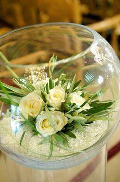 Hermoso centro de mesa en una pecera y rosas blancas