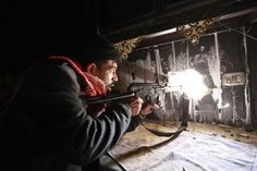 A Free Syrian Army fighter takes up position inside a burnt room in the Aleppo district of Salaheddine, November 12, 2012.  REUTERS/Zain Karam