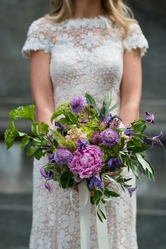 Garden style wedding bouquet in pink and purple with peonies, viburnum, scabiosa, olive, and clematis.