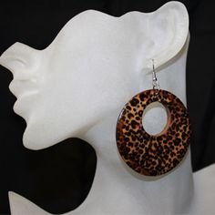 """Leopard earrings, leopard print earrings.  The leopard print earrings are brown with a small touch of orange to accentuate the double side painted pattern. This earring is painted wood so the details and patterns vary giving it a hand painted look.  The safari hoop earring is approximately 2 1/2"""" inches in diameter and hang about 2 1/2"""" inches long. You can spice up any outfit with these inexpensive accessories. Everyday cheap price of only $1.25 pair."""