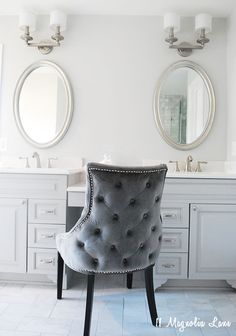 A pretty master bathroom renovation. See how this dated, 90's grade builder bath got a beautiful makeover with new marble tile, a new shower and custom vanity. This beautiful velvet chair and all bathroom accents came from HomeGoods. Sponsored Pin.