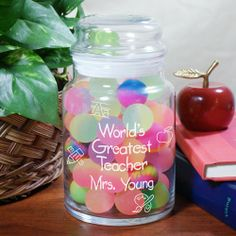 "Engraved World's Greatest Teacher Glass Treat Goodies Jar. Give your favorite teacher a lovely, personalized teacher gift which will look great in the classroom or at home. Our Personalized World's Greatest Teacher Treat Jar is perfect for storing classroom rewards including stickers, candy or little play toys. Your Engraved Teacher Candy Glass Jar measures 5.5""H x 4""W and holds 26 oz. Each glass jar comes with an air-tight glass lid."