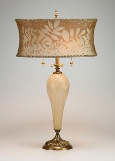 Lauren by Susan Kinzig and Caryn Kinzig: Mixed-Media Table Lamp available at www.artfulhome.com The Lauren table lamp is made with creamy blown glass. It has a corset shaped oval shade which is covered with woven jacquard in a two tone leaf pattern. It is adorned with beaded pulls and a beaded finial.