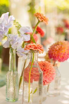 {details} vintage bottles of blooms. photography: http://www.megmanion.com/ #seacoast #newhampshire #newengland #wedding #centerpiece #coral #pink #lavender #flowers #vintage #bottles #dahlias #zinnias #sweetpea