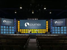 Adam Neal from Journey Church in Raleigh, NC brings us this very squarey design. They designed this set for the grand opening of their expanded facilities, new worship album, and new service times. They wanted full coverage and a wow factor without taking up any floor space. They got the white squares cut at Home Depot (cost around $350). Then they screwed 1x2s against the walls of the stage and used velcro to stick the squares to the wall. (A powered nail gun would be a more secure setup.)…