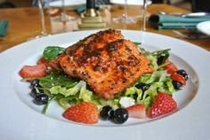 Menu Item: Eastern Glaze Alaskan Salmon served with spinach and fresh berry salad, tossed with red onion, cherry tomatoes and coriander vinaigrette.