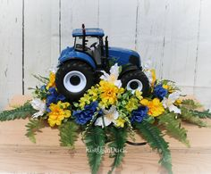 A unique tractor cemetery saddle with blue, yellow and white flowers and greenery, featuring a Blue tractor. This item is made to order. Flower may vary a little, but will be similar. If you have something you would like changed, please contact us. Measures approximately 21 inches in length and 12 inches high. The saddle is shipped flat so you can bend it to a perfect fit. It has rubber covers to avoid scratching. PLEASE CONTACT ME ABOUT SHIPPING. IT IS NOT ALLOWING ME TO ADD FEDEX HOME DELIVERY Grave Flowers, Cemetery Flowers, Funeral Flowers, Silk Flowers, Funeral Arrangements, Flower Arrangements, Floral Arrangement, White And Blue Flowers, Blue Yellow