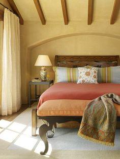 chambre à coucher avec peinture murale couleur sable, lit en bois avec literie…