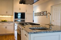 this busy kitchen island includes a gas cooktop with wall oven underneath as well as a prep sink and faucet. A nearby microwave and wall oven ensure this kitchen has plenty of cooking power.