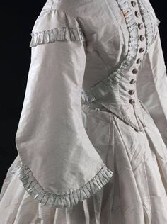 """Historical Sewing 1861-62 day dress from the Musee Galliera. Nice simple trim design of about 1.25"""" pleated silk. Notice the bodice is a plain 2-dart, pointed front but the placement of the trim on the surface mimics that very fashionable zouave jacket of the era."""