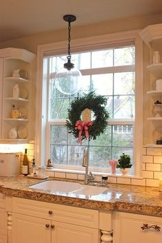 Quant (sp?) picture of a sink window during the holidays. I love the look of the hanging Globe Fixture over the Kitchen sink.