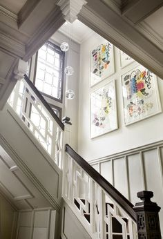 there's something about this stairwell. windows + dark wood + light walls + railing detail + colourful art. love it.