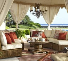 Grand Mediterranean cabana in outdoor patio design featuring incredible outdoor tenting with outdoor drapes and ornate chandelier hanging over seagrass furniture in a woven sectional and coffee table set. Outdoor Drapes, Outdoor Rooms, Outdoor Living, Outdoor Furniture Sets, Outdoor Decor, Garden Furniture, Furniture Design, Outdoor Chandelier, Wicker Patio Furniture