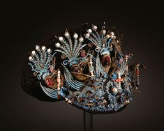 A BEJEWELED KINGFISHER FEATHER-EMBELLISHED HEADDRESS, CHAO GUAN. Qing Dynasty. The cap formed by black silk-covered wire and black silk mesh decorated with delicate spring-mounted motifs inlaid with kingfisher feathers, the front with a row of five gilt-metal phoenix inlaid with tourmalines, pearl, coral and turquoise tassels suspended from their beaks above two dragons confronted on a flaming pearl, all enhanced by pearls and further pink tourmaline