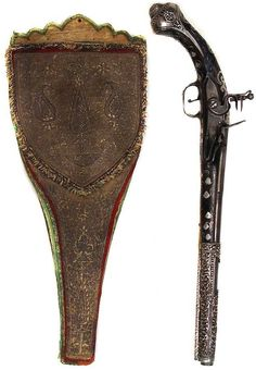 Ottoman flintlock kubur (holster pistol) and kuburluk (holster), 18th c, dark, lustrous walnut stock elegantly inlaid overall with engraved silver plaques and flowering vines, silver mounts wrought in scrolling vinework motifs. The flintlock mechanism and octagonal-breech barrel engraved with scrolling vines, leather kuburluk (holster) with green shagreen borders, the obverse covered in fine Ottoman silver embroidery with characteristic motifs including the Tree of Life, overall length 53.2…