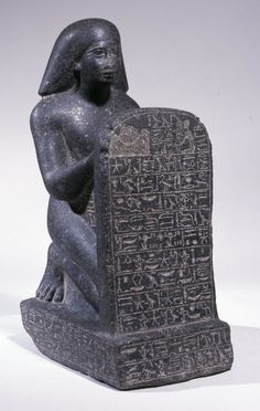 Grey granite stelophorous statue of Amenemheb, called Meh: the deceased is shown wearing a long wig, kneeling on a pedestal and holding a stela before him; the stela, connecting pillar between stela and figure, and the front, back and sides of the pedestal are all inscribed with hieroglyphs; the nose of the figure is damaged. The nose ofthe figure is mutilated and there are small abrasions around the bottom of the pedestal.