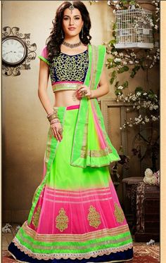 We unfurl our intricacy and exclusivity of creations highlighted in this mesmerizing florescent green & pink net lehenga choli. The Lovely Resham, Stones & Velvet Patch Work Throughout The Attire Is Awe-Inspiring. Bollywood Lehenga, Pink Lehenga, Net Lehenga, Lehenga Style, Lehenga Choli Online, Bridal Lehenga, Lehenga Choli Designs, Wedding Sarees Online, Sarees Online India