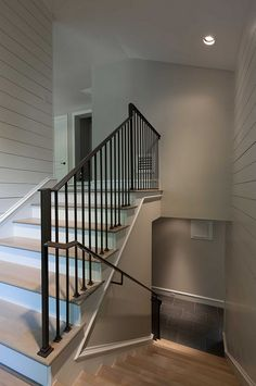 Staircase shiplap walls, white oak hardwood floors with whitewash finish and wrought iron stair balusters and handrail.