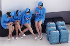 Models use mobile phones as they wait for the start of a promotion event by Thailand's second mobile network DTAC at a shopping centre in Bangkok, Thailand. (Narong Sangnak / EPA)