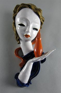A Goldscheider Art Deco pottery mask, modelled with a woman in a blue dress holding a vase, marked number 6859, incised K SOLD FOR £440