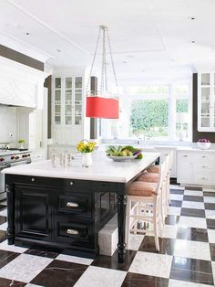 Intricate molding details, rich marble countertops, and a classy black-and-white marble tile floor exude elegant, traditional style in this upscale kitchen.