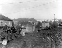 December 23, 1944; Battle of the Bulge - A 7th Armored Division antitank gun covers the approach on a road to Belgium; railroad crossing near Vielsalm, Belgium.