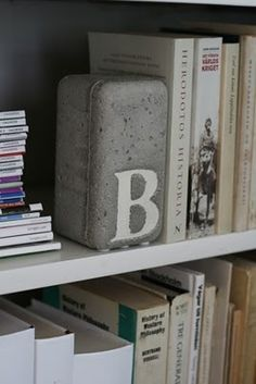 Concrete bookends, made in plastic container with a letter laid on the bottom before concrete is poured in.