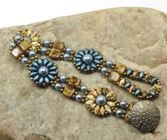 A charming bracelet in a floral design beaded with Czech glass beads. The floral motifs consist of petrol and opaque white picasso Super Duos surrounding a Czech glass pearl in steel blue. The floral motifs are separated with steel blue glass pearls and Czechmate Tiles in light beige picasso. All are embellished with Toho antique bronze seed beads. The clasp is a Super Duo beaded loop that slides over a light antique bronze decorative button.  When its clasped it measures 7 1/8 around an...