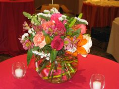 Bubble Bowl Design that keeps Colors and Style from Wedding Party Bouquets: Orange Lilly, Roses, Carnations and Snaps
