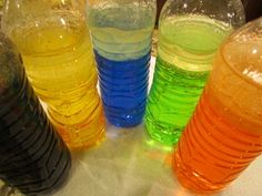 To make the colorful rainbow bottles, we simply filled the bottles about 3/4 of the way with water, added about 1/2 cup of cooking oil, and then added a few drops of food color. Then we used hot glue to permanently attach the lids so they wouldn't open up while the children played….