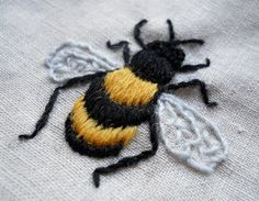 a perfectly embroidered bee by Sarah Homfray => note L stitching. Looks like a line of padding under each band as well. E.R.