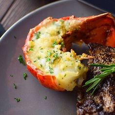 Steak and lobster. A super easy surf and turf recipe for two, made with buttered, baked lobster tails and a pan-seared NY strip steak cut in two. Steak And Lobster, Steamed Lobster, Baked Lobster Tails, Ny Strip Steak, Pan Seared Scallops, Surf And Turf, Roasted Garlic, Garlic Parmesan, Herb Butter